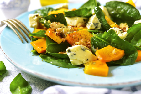 Pumpkin salad with spinach,blue cheese and nuts on a light background. Stock Photo