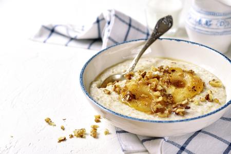 Bouillie d?avoine avec poire et noix caramélisées dans un bol vintage sur un fond d?ardoise, de pierre ou de béton.