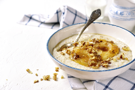 Oat porridge with caramelized pear and nuts in a vintage bowl on a light slate,stone or concrete background.