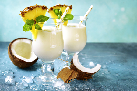 Traditional caribbean cocktail pina colada in a glasses on a blue slate,stone or concrete background.