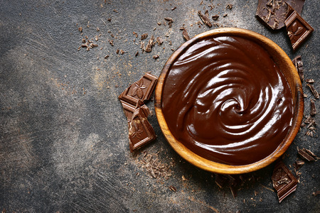 Chocolate ganache in a wooden bowl on a dark slate or rusty metal background.Top view with copy space.