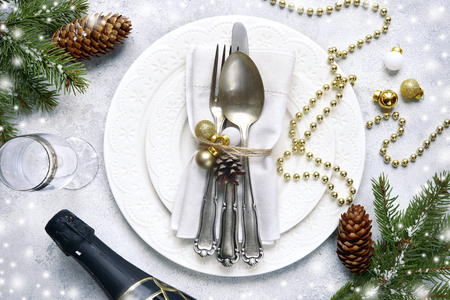 Christmas table place setting with christmas pine branches and plate, kine, fork and spoon on a light slate,stone or concrete background.Christmas holiday background.Top view.