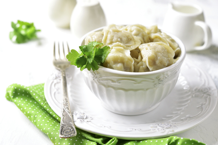 Pelmeni (dumplings stuffed with minced meat)-  traditional dish of russian cuisine in a white bowl on a light background. Stock Photo