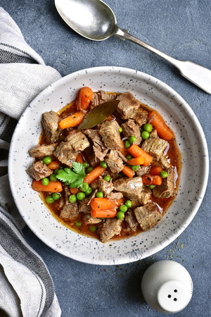Meat stew with carrot and green pea in a white bowl over dark grey slate or stone background.Top view.