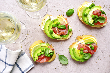 Delicious toasts with salted salmon, avocado, green pea and soft cheese on a light slate, stone or concrete backdrop.Top view with copy space.