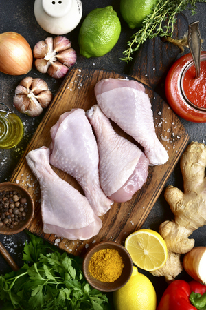 Raw organic chicken legs with ingredients for cooking (marinating) on a wooden cutting board over dark slate, stone or concrete background.Top view. Banque d'images
