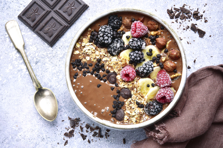 Chocolate banana smoothie bowl with frozen berries and granola on a light grey slate, stone or concrete background.Top view.