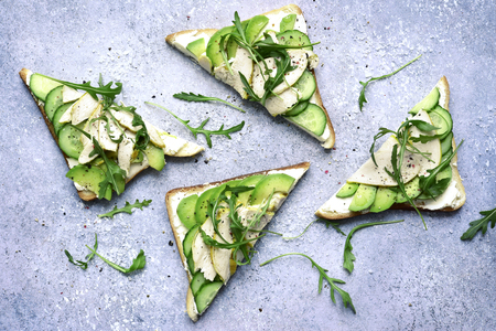 Sandwichs with soft cheese, avocado, cucumber, arugula and grilled chicken breast on a grey slate, stone or concrete background.Top view with copy space.