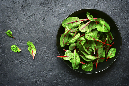 Chard leaves  in a bowl on a black slate, stone or concrete background.Top view with copy space. Stock Photo