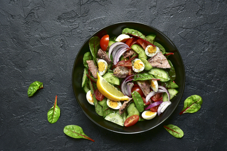 Vegetable salad with tuna fillet in a black bowl on a dark slate, stone or concrete background.Top view.