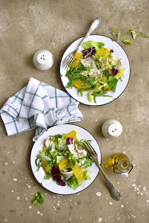 Detox salad from mix of salad leaves, chicken fillet and oranges on a plates over beige (sand) slate, stone or concrete background.Top view with copy space.