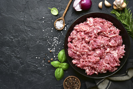 Homemade minced meat in a black bowl over dark slate or stone background with ingredients for making.Top view with copy space.