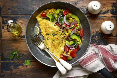 Omelette stuffed with vegetables in a black skillet for a breakfast over dark wooden background.Top view .