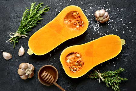 Halves of raw organic butternut squash with spices and ingredients for making on a black slate, stone or concrete background.Top view. Stock Photo