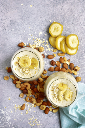 Homemade banana nut smoothies with ingredients for making over light grey slate, stone or concrete background.Top view with copy space.