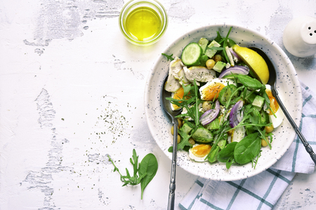 Green vegetable salad with chickpea,chicken fillet and boiled eggs on a white slate, stone or concrete background.Top view with copy space. Stock Photo