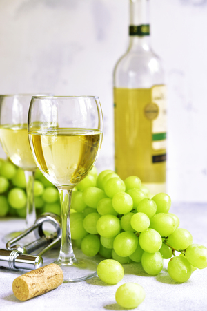 Two glasses of white wine,cheese and grapes on a light cocncrete,stone or slate background.