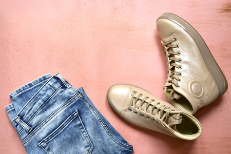 Woman clothing set - boots and  blue jeans on a pastel slate, stone or concrete background.Top view with copy space.