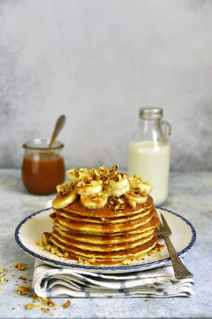 Homemade hot banana pancakes with caramel sauce and nuts on a vintage plate over light slate, stone or concrete background.