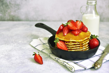 Homemade delicious pancakes with maple syrup and fresh ripe strawberry in a skillet pan over light slate, stone or concrete background. Фото со стока