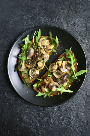 Rye toasts with sauteed mushrooms on a black plate over dark slate, stone or concrete background.Top view.