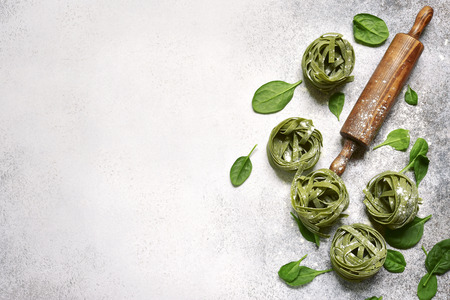 Food background with homemade spinach pasta tagliatelle, wooden rolling pin and spinach leaves on a light grey slate, stone or concrete backdrop.Top view with copy space.