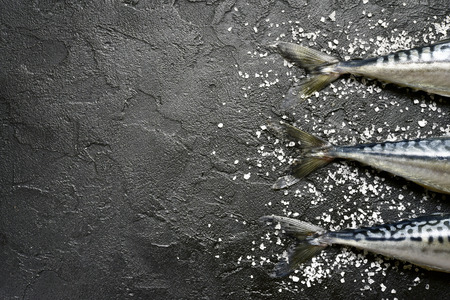 Whole raw organic fish mackerel with sea salt on  a black  slate, stone or concrete background.Top view with copy space.