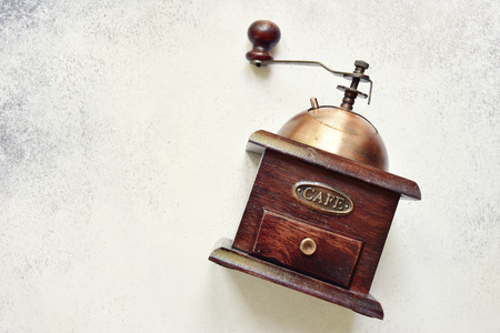 Antique vintage retro wooden coffee grinder with ingredient for making drink on a light slate, stone or concrete background.Top view with copy space.