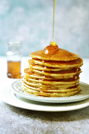 Stack of homemade delicious pancakes with maple syrup for a breakfast on a plate on a light blue slate, stone or concrete background. Foto de archivo
