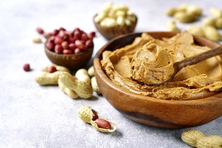 Homemade peanut butter with assortment of nuts in a wooden bowl on a light grey slate, stone or concrete background.