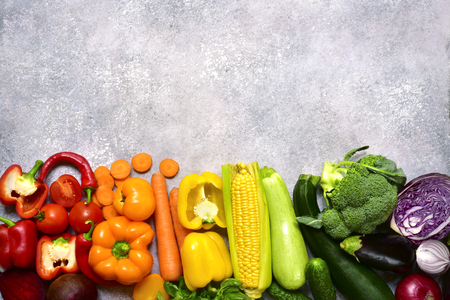 Food background with colorful vegetables (tomato, beetroot, bell pepper, cucumber,zucchini, broccoli, eggplant) on a light grey slate, stone or concrete table.Top view with copy space. Stock Photo