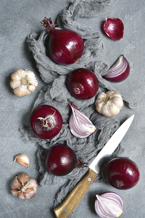 Organic red onion and garlic with a knife on a grey slate,stone or concrete background.Top view with space for text.