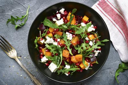 Salade de potiron à la betterave, à la roquette et au fromage feta dans un bol noir sur fond d'ardoise gris foncé, de pierre ou de béton.Vue de dessus.