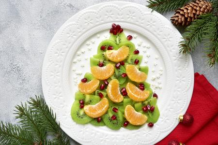 Árbol de navidad comestible de kiwi y rodajas de mandarina en un plato blanco sobre fondo claro de pizarra, piedra u hormigón.Vista superior con espacio de copia.