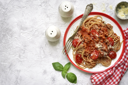 Whole wheat spaghetti bolognese on a plate over white slate, stone or concrete background.Top view with copy space.