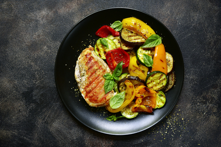 Grilled chiken fillet with vegetables in a black bowl over dark slate, stone or concrete background.Top view.