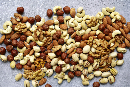 Assortment of nuts on  a light slate or stone background - healthy snack.Top view with copy space.