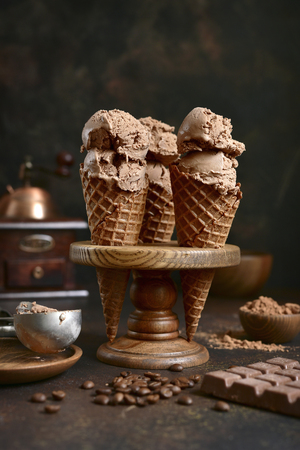 Chocolate coffee ice cream in a waffle cone on a dark slate, stone or concrete background.