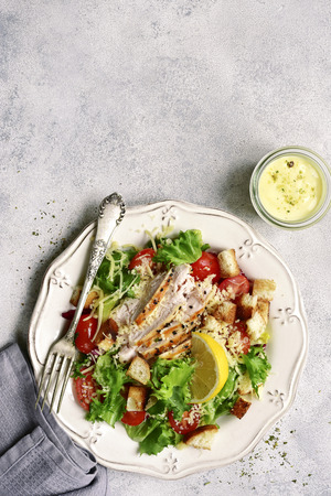 Caesar salad with grilled chicken, parmesan cheese, croutons and cherry tomatoes on a white vintage plate over light slate, stone or concrete background.Top view with copy space.