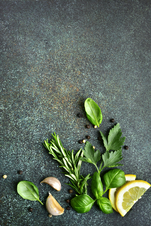 Variety of spices : herbs, garlic, black pepper, lemon on a dark emerald slate, stone or concrete background.Top view with copy space.