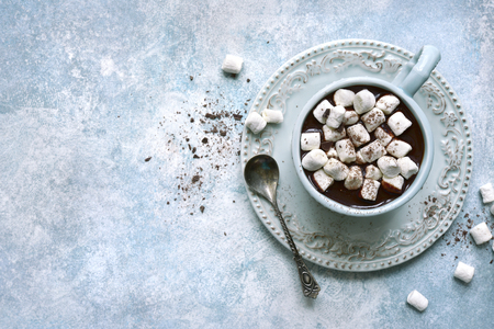 Homemade hot chocolate with mini marshmallow in a vintage cup over light blue slate, stone or concrete background.Top view with copy space. Stock Photo