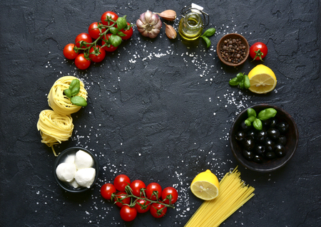 Food background with traditional ingredients of mediterranean cuisine over black slate,stone or concrete backdrop.Top view with copy space.
