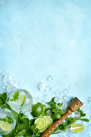 Homemade citrus lemonade mojito with ingredients for making on a light blue slate, stone or concrete background.Top view with copy space. Stock Photo