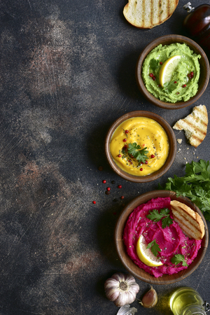 Assortment of hummus on a dark slate, stone or concrete background.Top view with copy space.