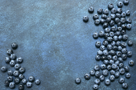 Food background with fresh blueberry on a dark blue slate, stone or concrete background.Top view with copy space.