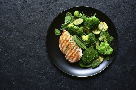 Grilled chicken fillet with green vegetable salad on a black slate, stone or concrete background.Top view with copy space.
