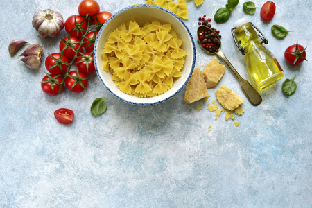 Traditional organic ingredients of italian cuisine : pasta, tomato, garlic, olive oil, parmesan cheese and basil on a light blue slate, stone or concrete background.Top view with copy space.