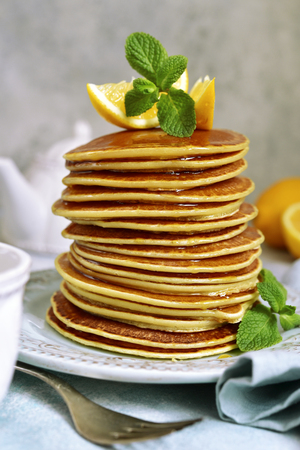 Stack of homemade lemon pancakes with honey and mint on a vintage plate over light blue slate, stone or concrete background.