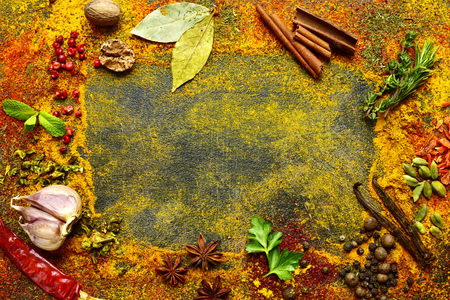 Assortment of natural spices scattered on a dark slate, stone or concrete background.Top view with copy space.