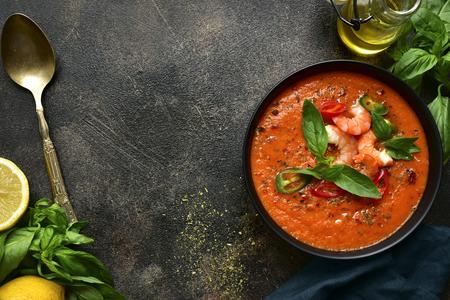 Délicieuse soupe de tomates aux crevettes dans un bol noir sur fond d'ardoise foncée, de pierre ou de béton. Vue de dessus avec espace de copie. Banque d'images